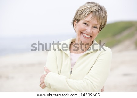 Woman at the beach with arms crossed smiling - stock photo