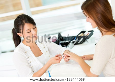 Woman at the beauty salon getting a manicure - stock photo