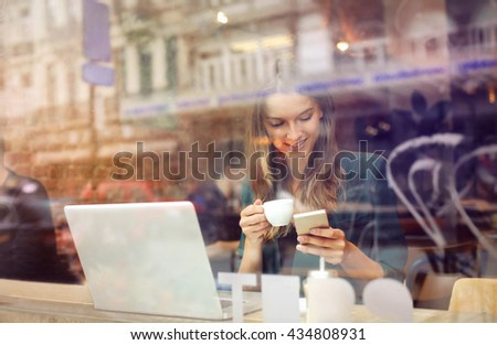 Woman at the cafeteria using technology