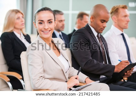 Woman at the conference. Group of business people in formalwear sitting at the chairs in conference hall and writing something gin their note pads while attractive woman looking at camera and smiling - stock photo
