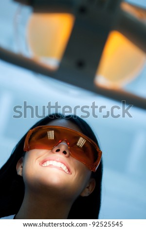 Woman at the dentist wearing laser glasses - stock photo