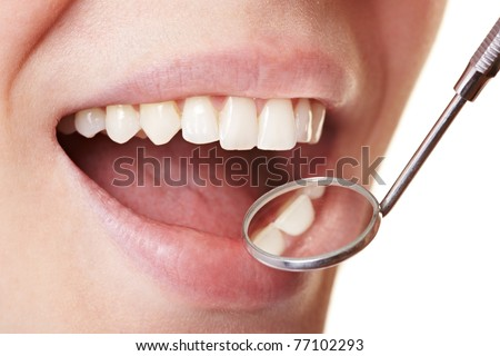 Woman at the dentist with mirror near her teeth - stock photo