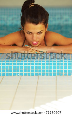 Woman at the Edge of a Swimming Pool looking down at copyspace - stock photo