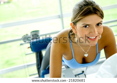 woman at the gym doing exercises on a machine for her bottom - stock photo