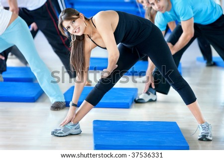 Woman at the gym doing stretching exercises - stock photo
