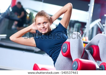 Woman at the gym exercising on a machine - stock photo