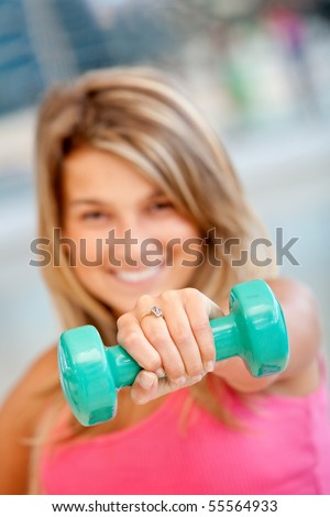 Woman at the gym lifting a free-weight in front of her face and smiling - stock photo