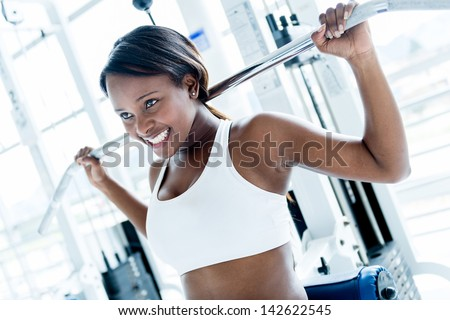Woman at the gym working out on a machine - stock photo