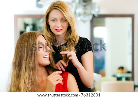 Woman at the hairdresser getting advise on her hair styling - stock photo