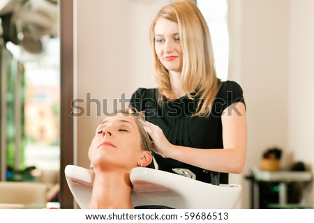 Woman at the hairdresser getting her hair washed and rinsed feeling visibly well - stock photo