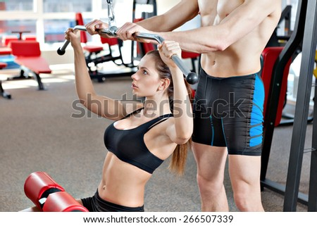 Woman at the health club with her personal trainer, learning the correct form on the pull down machine. - stock photo