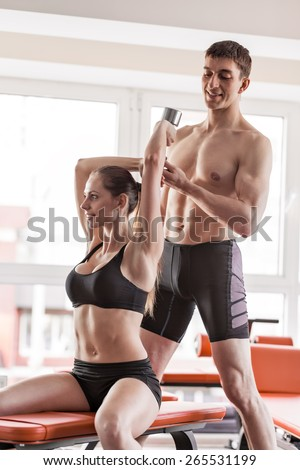 Woman at the health club with her personal trainer, learning the correct form with barbell - stock photo