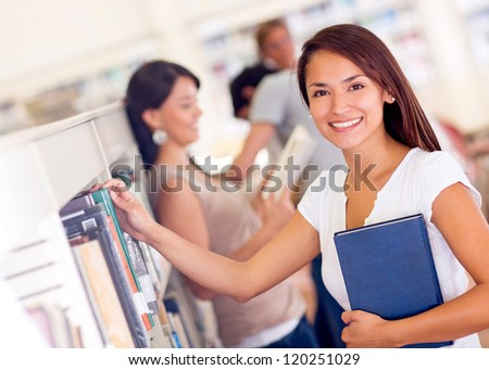 Woman at the library taking a book and smiling - stock photo