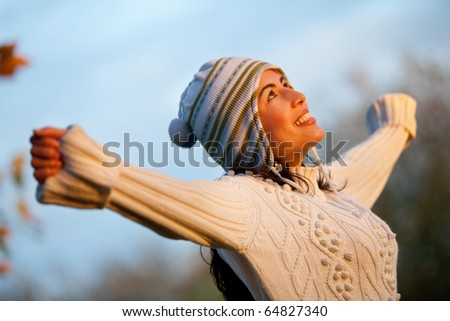 Woman at the park with arms open wearing warm clothes - stock photo