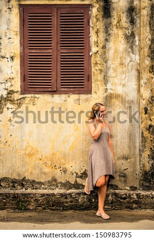 Woman at the phone on the streets of an old city - stock photo