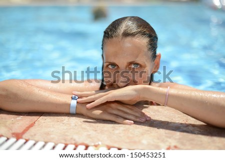 Woman at the side of the pool - stock photo