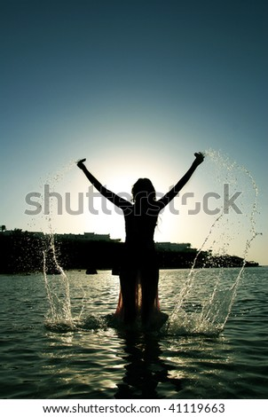 Woman at the sunrise/sunset droping water. Joy, freedom, healthy lifestyle concept