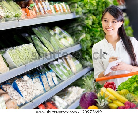 Woman at the supermarket with a shopping list - stock photo