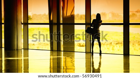 woman at the window at the airport - stock photo
