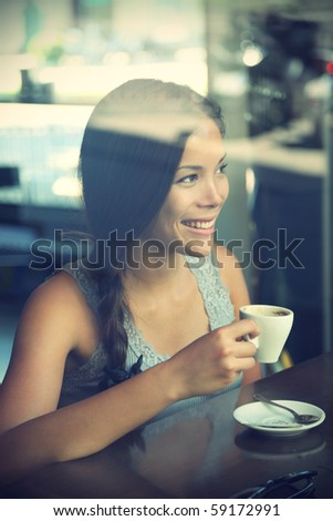 Woman at trendy cafe drinking coffee. Young beautiful Caucasian / Asian model. Reflections from windows. Image cross processed. - stock photo