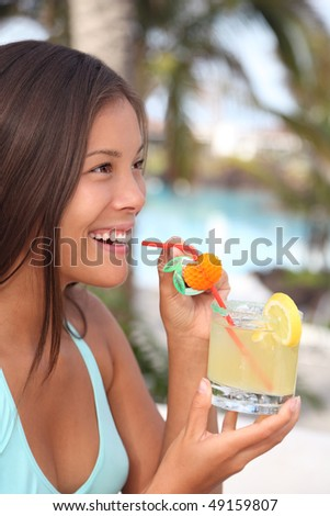 Woman at tropical resort having a Caprihinia drink. Beautiful smiling mixed race caucasian / chinese young woman model