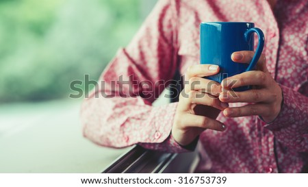Woman at window holding a cup and having a relaxing coffee break, hands close up - stock photo