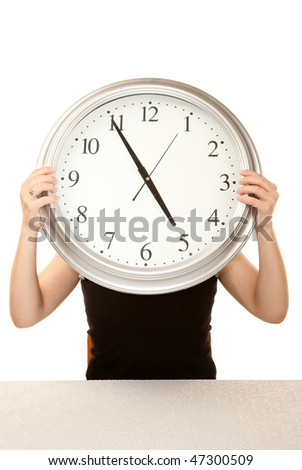 Woman at work holding up large office clock - stock photo