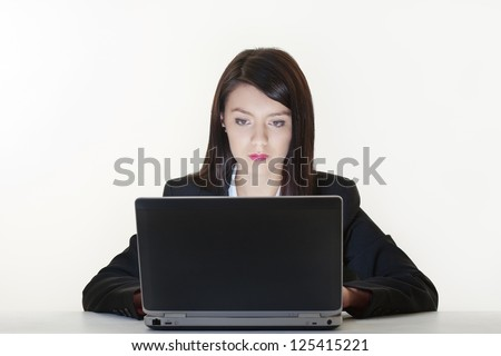 woman at work on a laptop with a light sources  coming from the computer screen - stock photo