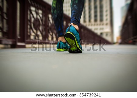 woman athlete feet and shoes while running in the city - stock photo
