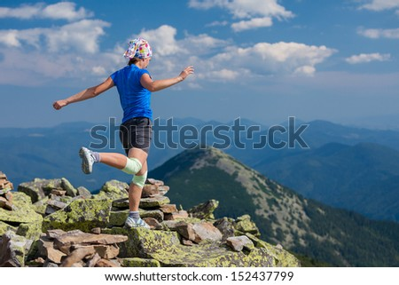 Woman athlete is jumping over stones in mountains - stock photo
