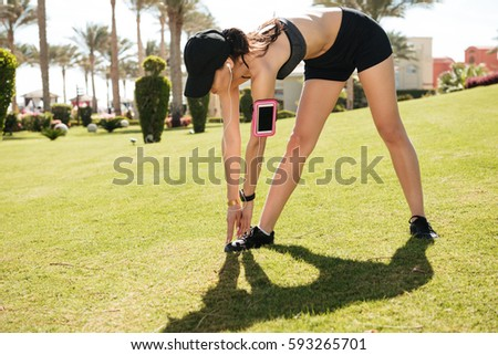 Woman athlete listening music from blank screen smartphone and doing exercises on lawn