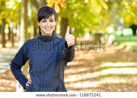 Woman athlete with thumbs up approving. Happy positive sportswoman in park outside. Caucasian brunette model looking friendly.