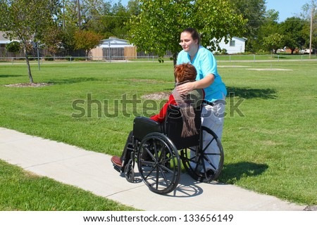 Woman attending to a patient in a wheelchair - stock photo