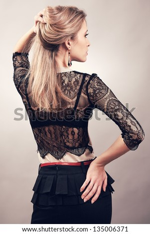 Woman back is turned in a stylish dress - stock photo