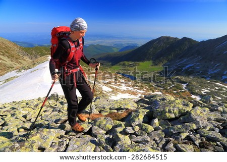 Woman backpacker on rocky mountain in sunny day of summer - stock photo