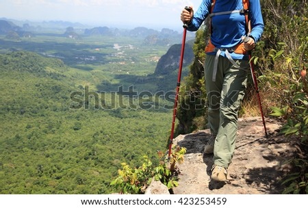 woman backpacker walking on mountain peak cliff
