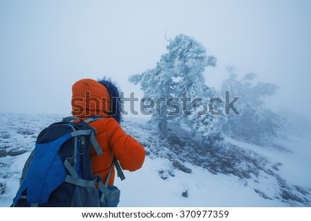 Woman backpacker walking on the snow in the winter in the mountains. Hiking in the Alps in the north in the cold.