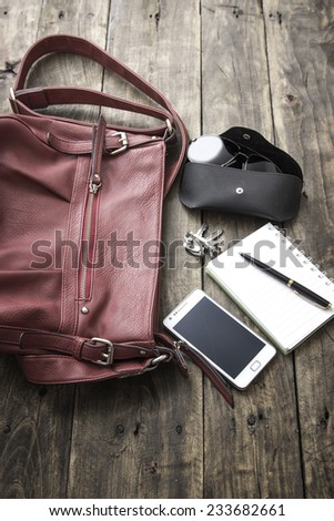 woman bag stuff, handbag over rustic wooden background - stock photo