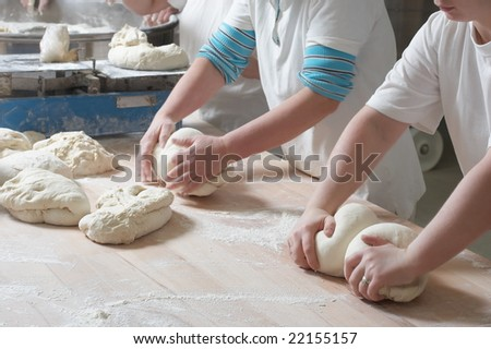 Woman bakery team at work mixing dough - stock photo