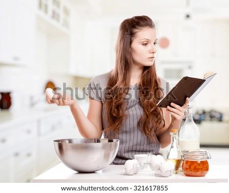Woman baking at home following recipe  - stock photo