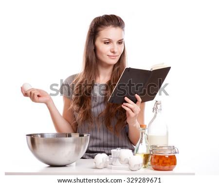 Woman baking at home following recipe . - stock photo