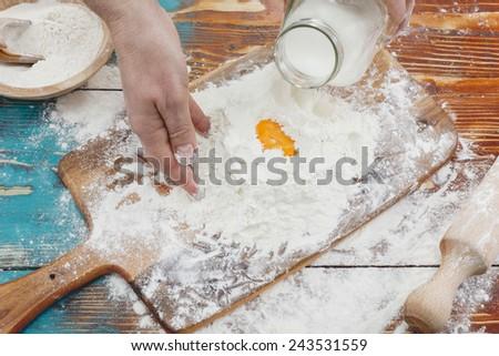 Woman baking. Woman pouring milk into flour as she prepares to bake - stock photo