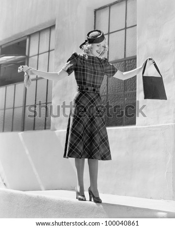 Woman balancing on edge of wall - stock photo