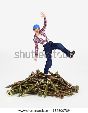 Woman balancing on pile of screws - stock photo