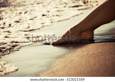 woman barefoot legs on sand beach by the sea at sunset, closeup,  selective focus, gold color - stock photo