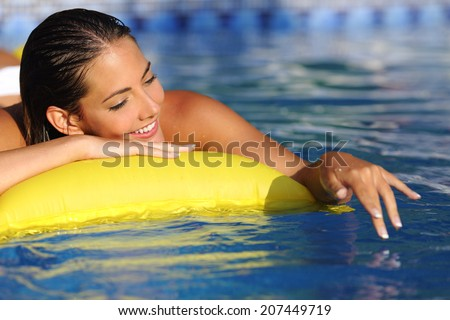 Woman bathing and playing on a mattress with water on a swimming pool in vacations               - stock photo