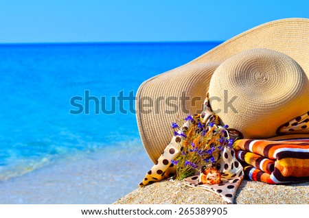Woman beach hat, bright towel and flowers against blue ocean background - stock photo