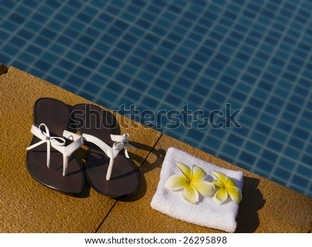 woman beach sandals with towel near the pool - stock photo