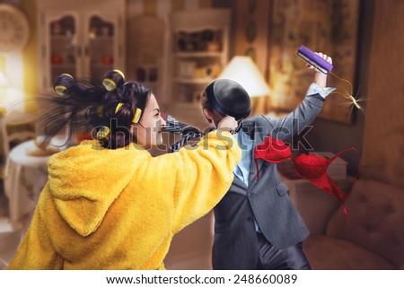 Woman beats her husband with pan - stock photo