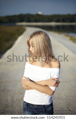 woman beautiful blond-haired serious looking direction. background on the shore of lake. - stock photo